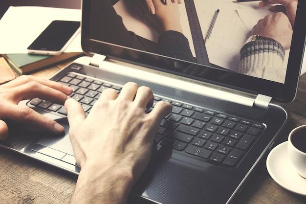 Homme travaillant sur un ordinateur portable sur une table en bois