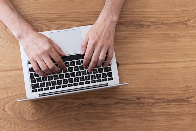 Homme travaillant sur ordinateur portable, vue de dessus sur les mains des hommes à l'aide d'un ordinateur portable