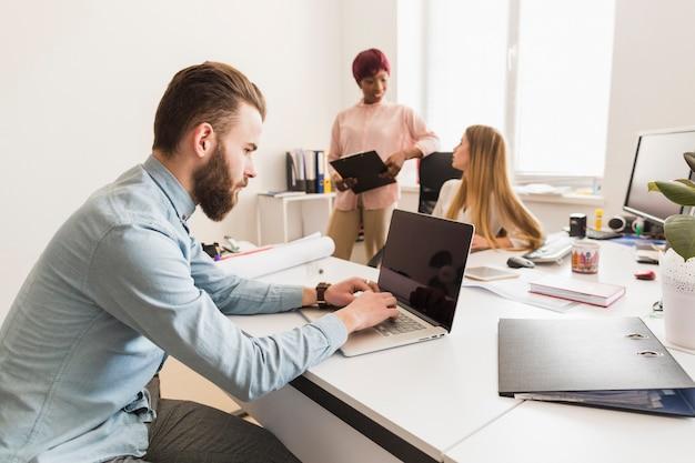 Homme travaillant près de collègues bavarder
