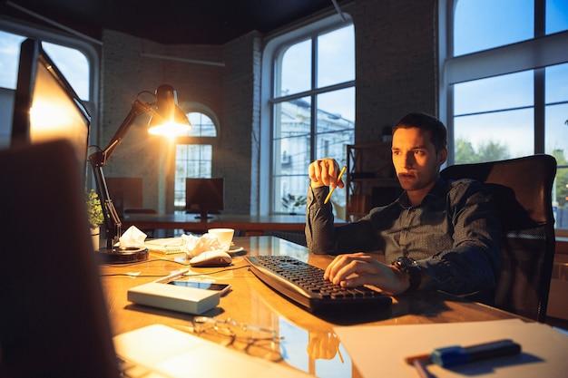 Homme travaillant seul au bureau, restant jusque tard dans la nuit.