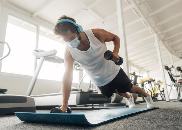 Homme travaillant sur tapis à la salle de sport
