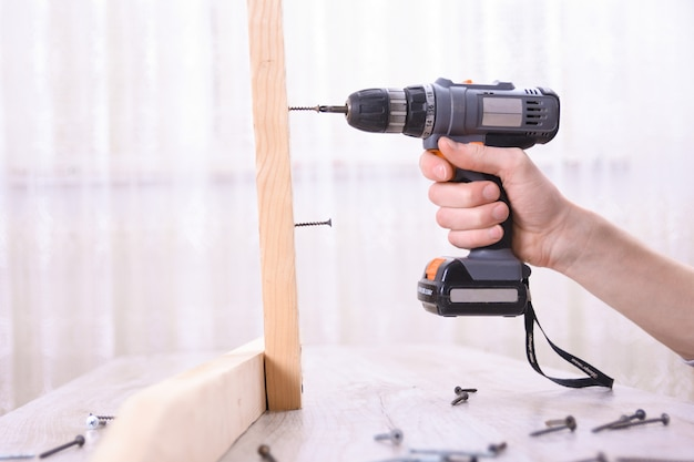 L'homme travaille avec l'assemblage de meubles à l'aide d'un tournevis électrique dans une nouvelle installation de maison - travail sur site de technicien à l'aide du concept d'outils à main