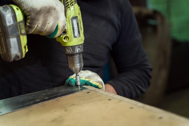 L'homme travaille en atelier automobile avec un tournevis sans fil