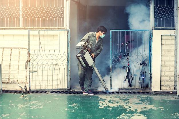 L'homme travaille à la brumisation pour éliminer les moustiques