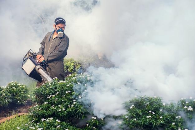 L'homme travaille à la buée pour éliminer les moustiques