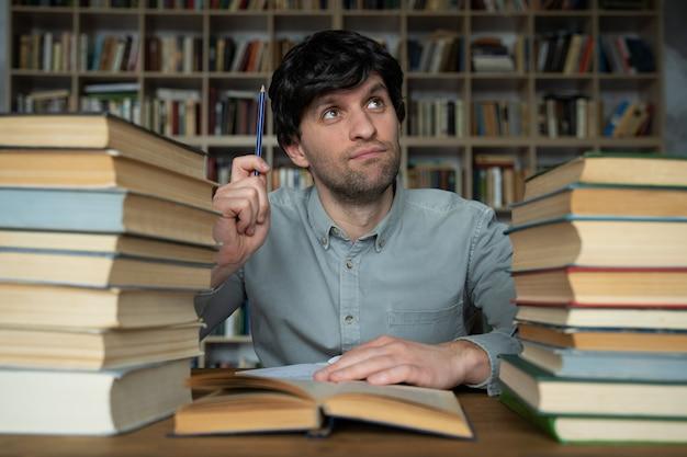 L'homme travaille à un bureau dans la bibliothèque ayant une excellente idée pointant son doigt vers le haut