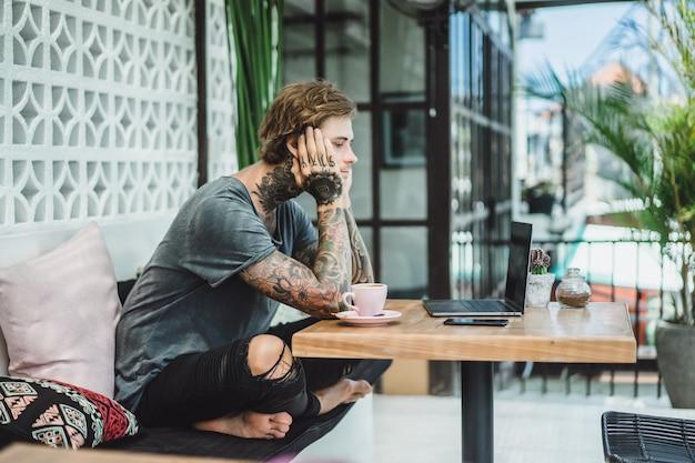 L'homme travaille dans un café. concept de freelance, café et ordinateur portable