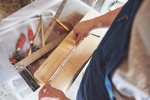 Un homme travaille dans une menuiserie, travaillant avec un arbre.