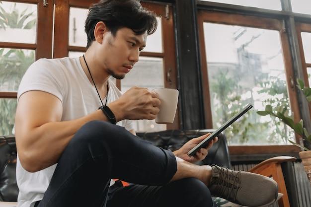 L'homme travaille dans un salon avec tablette et café concept de staycation