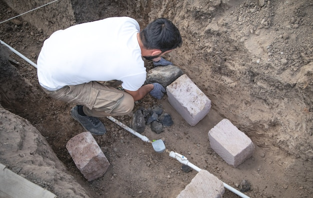L'homme travaille un mur de pierre sur un trou dans le sol.