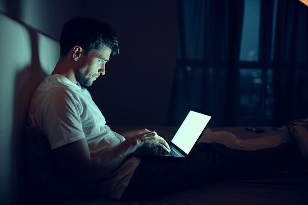 Un homme travaille sur un ordinateur portable au lit, une femme bien-aimée dort, le travail de nuit, la trahison