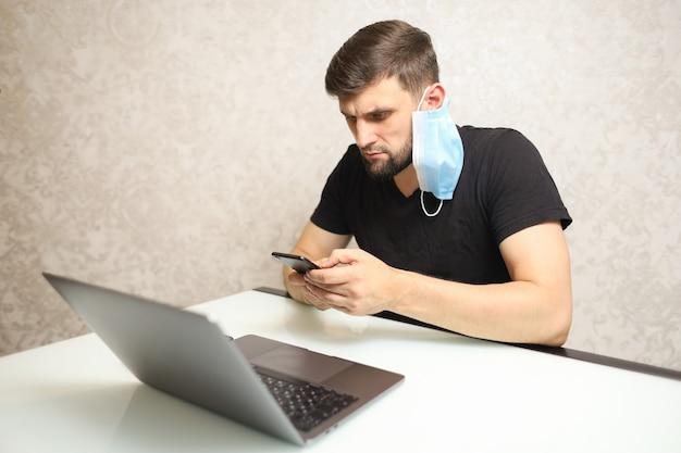Un homme travaille sur un ordinateur portable à la maison en isolement et a un masque médical suspendu au-dessus de son oreille