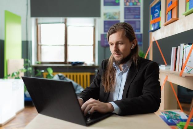 Un homme travaille sur son ordinateur portable dans un environnement de bureau coloré