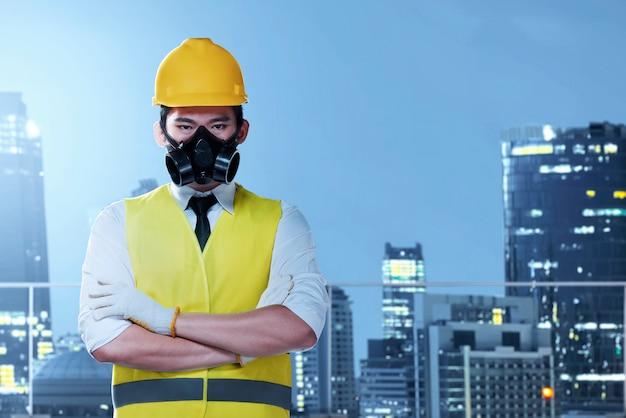 Homme travailleur asiatique avec un masque de protection et un casque jaune debout
