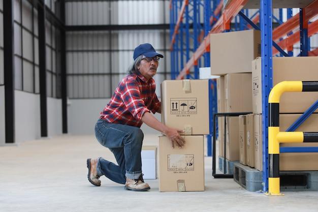 Homme travailleur asiatique soulever une boîte lourde en usine