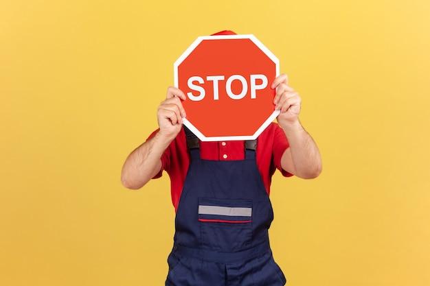 Homme travailleur couvrant le visage tenant un panneau de signalisation d'arrêt, avertissant du danger, des restrictions et des limites