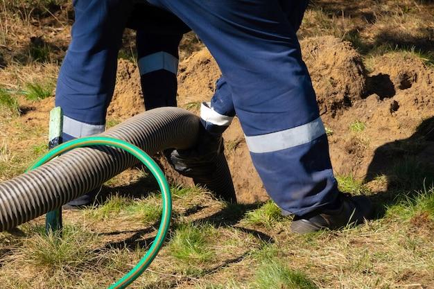 Homme travailleur tenant un tuyau, fournissant un service de nettoyage des égouts en plein air. la machine de pompage des eaux usées débouche le trou d'homme bloqué