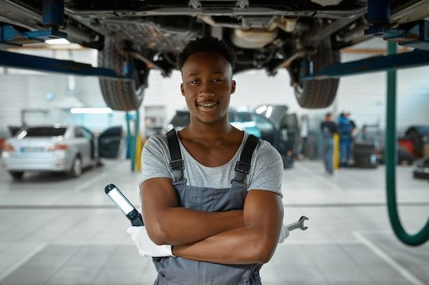 L'homme travailleur vérifie la suspension de la voiture dans l'atelier mécanique