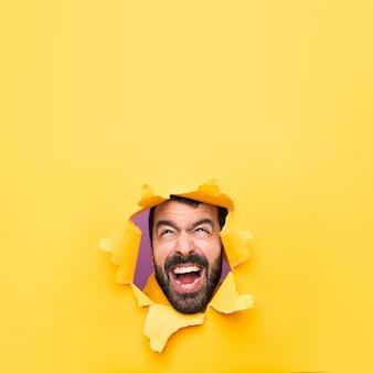 Homme à travers un trou de papier