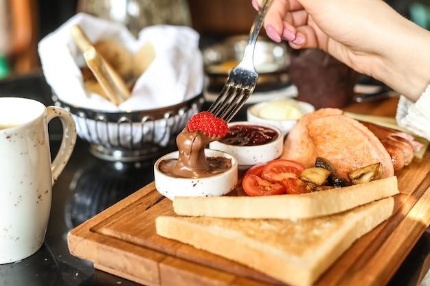 L'homme trempe la fraise dans le beurre au chocolat petit-déjeuner ensemble toast tomate miel vue latérale
