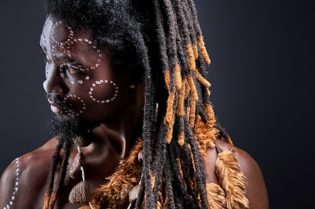 Homme tribal avec des dreadlocks à côté, en contemplation, en pensant à quelque chose d'isolé