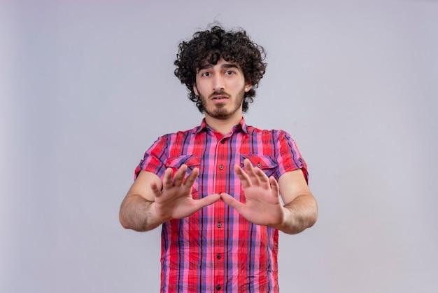 Un homme triste aux cheveux bouclés en chemise à carreaux essayant d'arrêter quelque chose