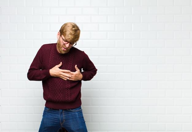 Homme à la triste, blessé et le cœur brisé, tenant les deux mains près du cœur, pleurant et se sentant déprimé