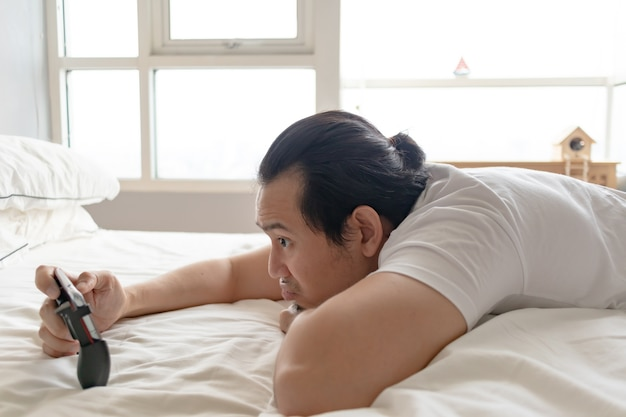 Homme triste et bouleversé accro au jeu mobile et le perdant tout en restant à la maison.