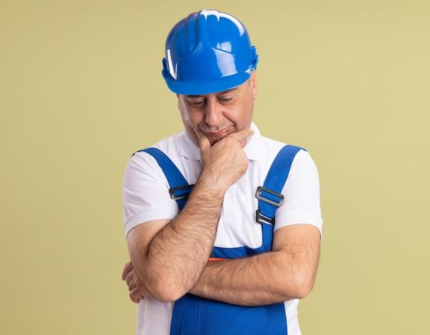 Homme triste constructeur adulte en uniforme met la main sur le menton et regarde vers le bas isolé sur mur vert olive
