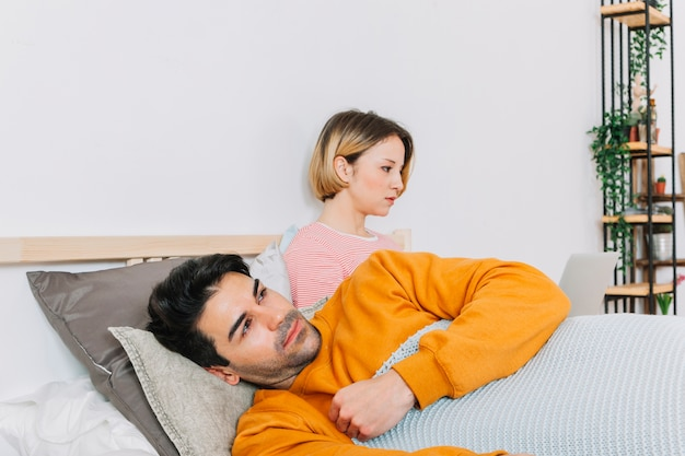Homme triste, couché près de femme avec un ordinateur portable
