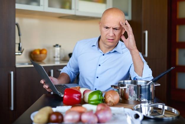 Homme triste cuisine avec l'aide de recette sur tablette