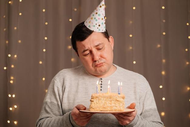 Un homme triste dans une casquette festive avec un gâteau d'anniversaire souffle des bougies. tristesse due au vieillissement et à l'anniversaire. ca c'est drôle.