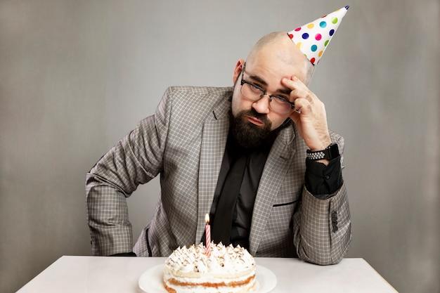 Homme triste dans un chapeau de carnaval avec un gâteau avec une bougie. fête noire.