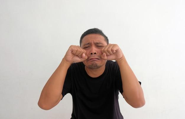 Homme triste drôle pleurant isolé sur fond blanc