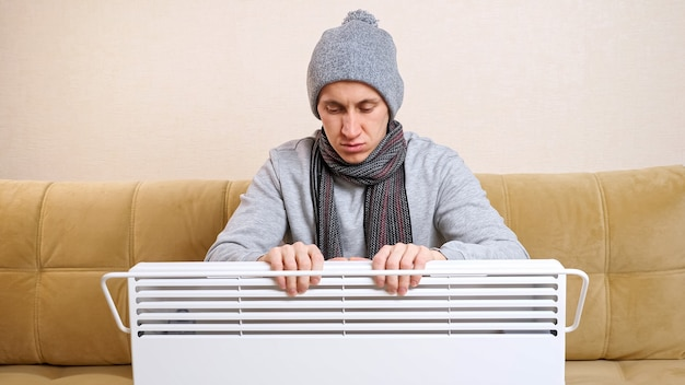 Un homme triste avec une écharpe et un bonnet tricoté se réchauffe les mains au-dessus du radiateur