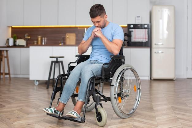 Homme triste en fauteuil roulant plein coup