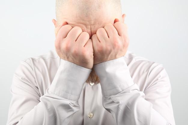 Homme triste avec les mains fermées le visage sur fond blanc