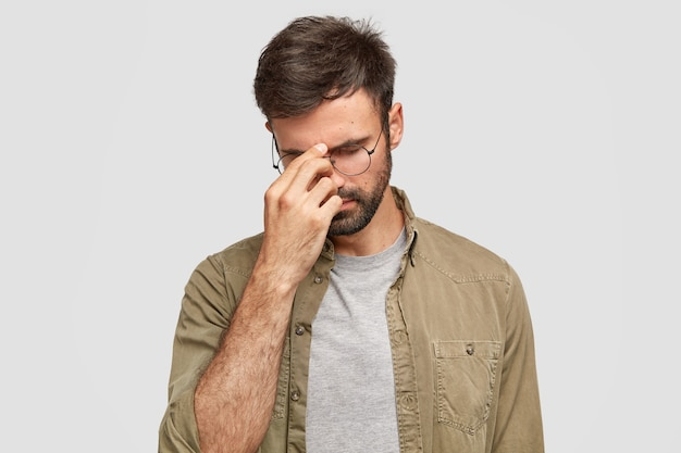Un homme triste et malheureux garde la main sur le nez, la tête baissée, essaie de se concentrer, a une expression surmenée