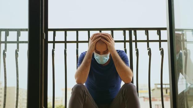 Homme triste avec masque jetable sur balcon parce qu'il a été testé positif pour le coronavirus.