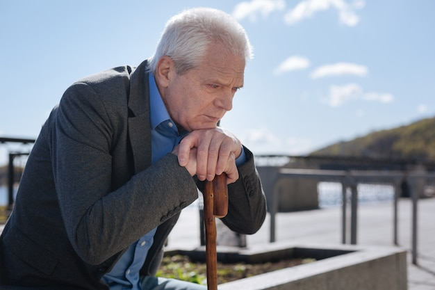 Homme triste et maussade calme, croisant les mains sur le bâton et se sentant bouleversé tout en regardant vers le bas et en pensant