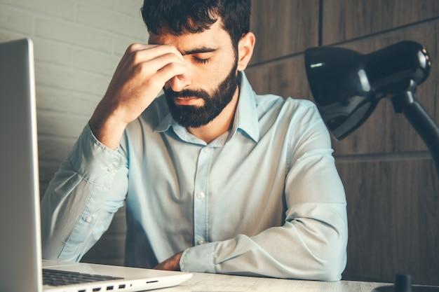 Homme triste et ordinateur au bureau