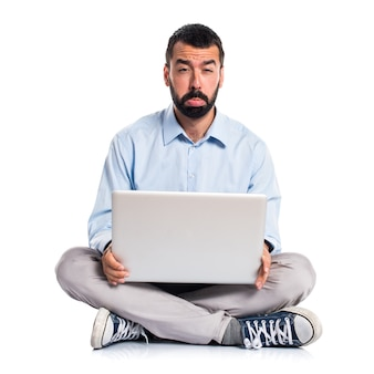 Homme triste avec un ordinateur portable