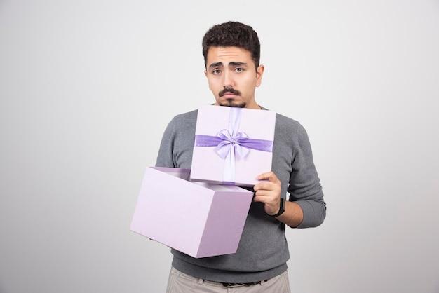 Homme triste ouvrant une boîte violette sur un mur blanc.