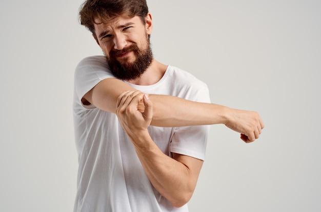 Homme en tshirt blanc douleur à la main anatomie traumatologie médecine