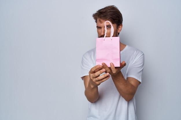 Homme en tshirt blanc paquet rose cadeau shopping
