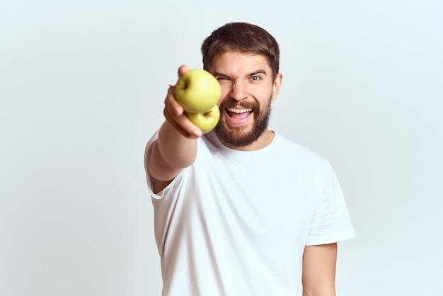 Homme en tshirt blanc pommes dans les mains fond clair de style de vie de fruits