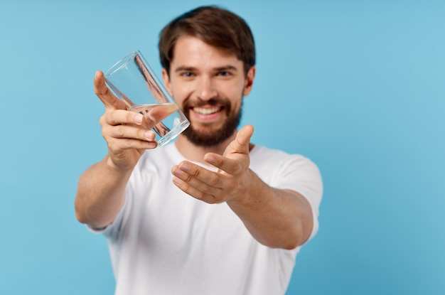 Homme en tshirt blanc verre d'eau fond bleu