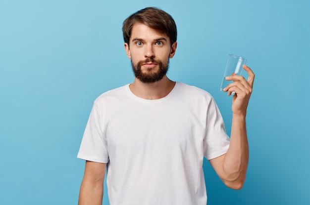 Homme en tshirt blanc verre d'eau studio
