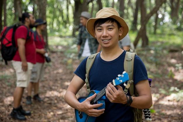 Homme avec ukulélé randonnée dans la forêt