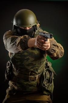 L'homme en uniforme avec une arme à feu posant, visant, rechargeant, tirant, sur un fond sombre dans le studio